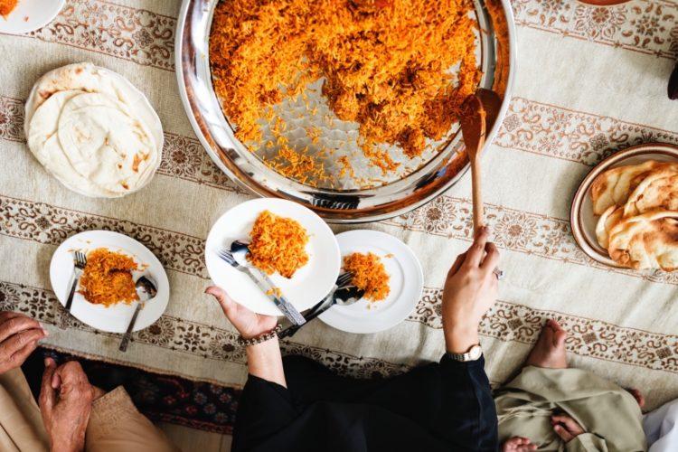 tavola apparecchiata con donna che serve Chicken Biryani